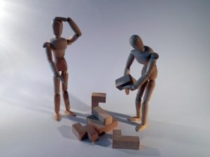 Toy men assembling something with frustration