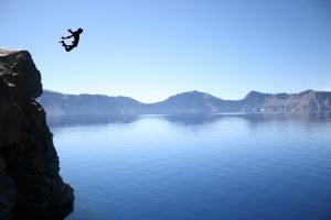 Man jumping off cliff into crater