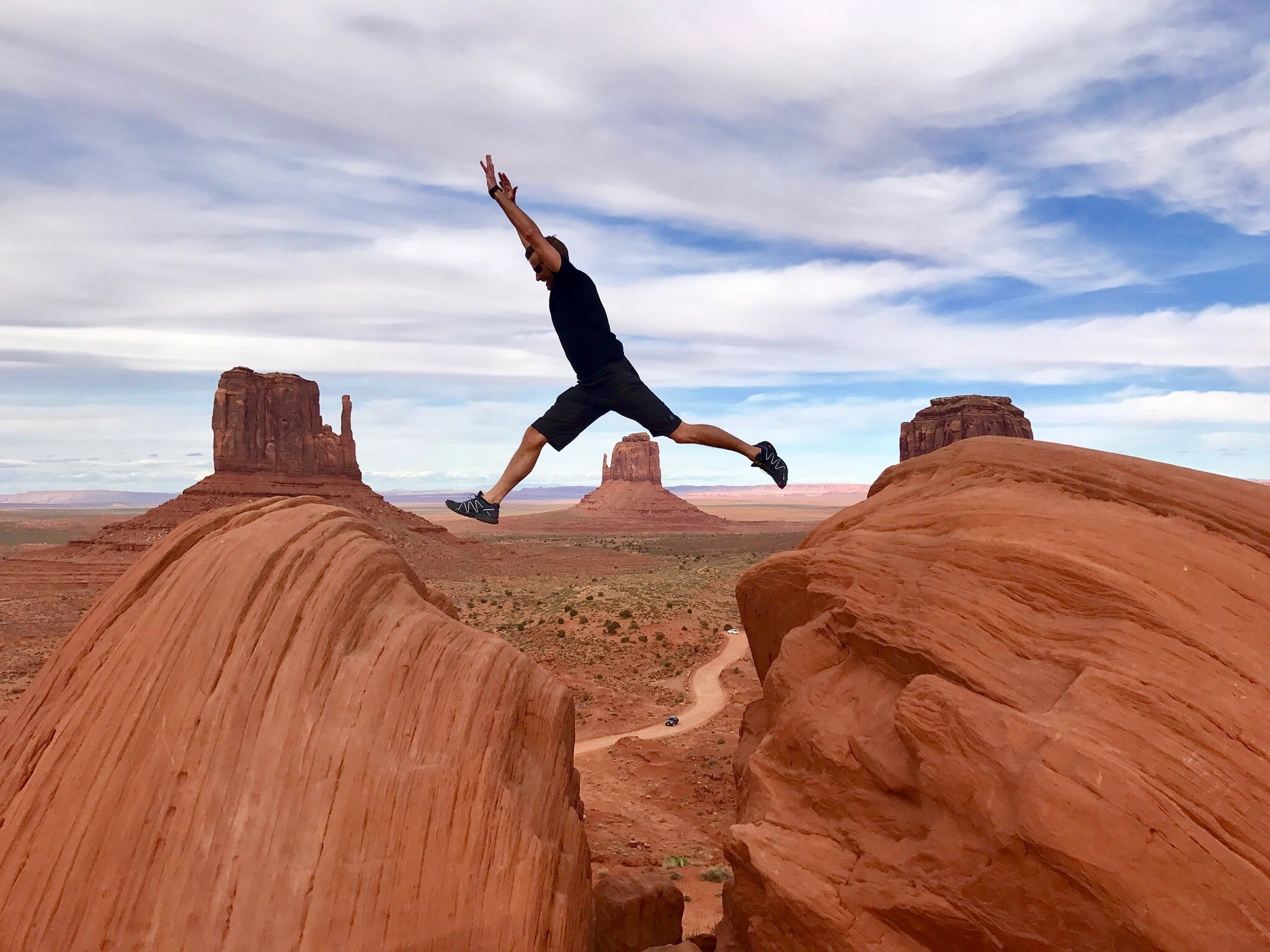 Man jumping rock formations in Utah with a gap between them.