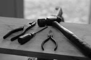 Collection of tools and hammer on a wooden board.
